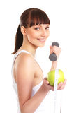 A young brunette with a dumbbell and an apple Stock Photo