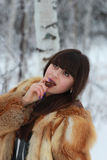 Young brunette eating candy in a winter forest. Young long-haired brunette eats candy in a winter forest Royalty Free Stock Photography