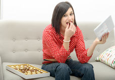 Young brunette eats chocolate Stock Images