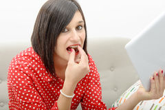 Young brunette eats chocolate Royalty Free Stock Images