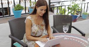 Content woman on vacation with laptop. Young brunette in elegant summer dress posing at table with glass of water near and browsing laptop working on vacation stock footage