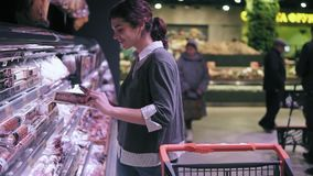 Young brunette female costumer looking at cellphone while walking through meat aisle in grocery store. Girl takes salami. Stick from the shelf and puts it into stock footage