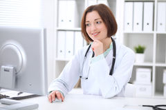 Young brunette female doctor sitting at a desk and working on the computer at the hospital office. Stock Images