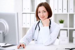 Young brunette female doctor sitting at a desk and working on the computer at the hospital office. Royalty Free Stock Photos