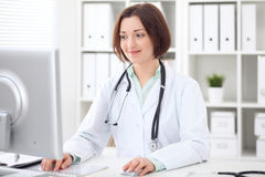 Young brunette female doctor sitting at a desk and working on the computer at the hospital office. Stock Image