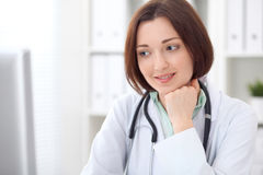 Young brunette female doctor sitting at a desk and working on the computer at the hospital office. Royalty Free Stock Images