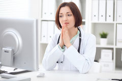 Young brunette female doctor sitting at a desk and working on the computer at the hospital office. Stock Photos