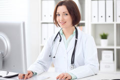 Young brunette female doctor sitting at a desk and working on the computer at the hospital office. Stock Photography