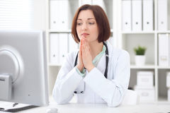 Young brunette female doctor sitting at a desk and working on the computer at the hospital office. Royalty Free Stock Image