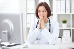 Young brunette female doctor sitting at a desk and working on the computer at the hospital office. Royalty Free Stock Photo