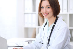 Young brunette female doctor sitting at the table and typing on laptop computer. Royalty Free Stock Images