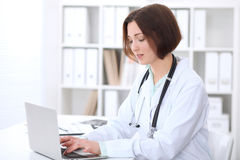 Young brunette female doctor sitting at the table and typing on laptop computer. Stock Photography