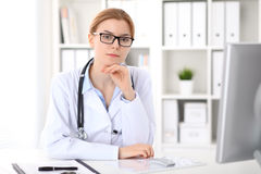 Young brunette female doctor sitting at the table and working by computer  at hospital office. Royalty Free Stock Photo