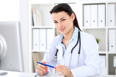 Young brunette female doctor sitting at the table and working by computer  at hospital office. Stock Photo