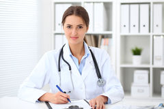 Young brunette female doctor sitting at the table and working at hospital office. Stock Images