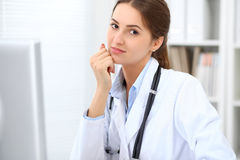 Young brunette female doctor sitting at the table and working at hospital office. Royalty Free Stock Photos