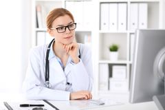 Young brunette female doctor at work in hospital. Physician ready to help. Medicine and healthcare concept stock photography