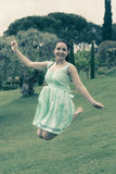 Young brunette female in dress jumping at the park Royalty Free Stock Images