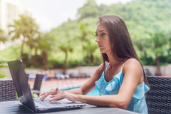 Young brunette female freelancer wearing casual clothes working on laptop typing  keyboard outdoors in summer, blurre Royalty Free Stock Image