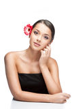 Young brunette female with gerbrera flower in hair. Vertical studio beauty portrait of young attractive brown-eyed brunette caucasian female with pink gerbera Stock Image