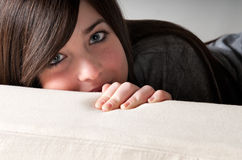 Young brunette female lean out sofa playful Royalty Free Stock Photos