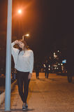Young brunette female leaning against lamppost on Stock Images