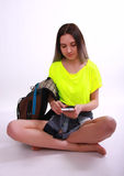 Young brunette female student sitting and looking at her smartphone. Stock Image