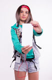 Young brunette female student standing and listening to music from your device. Beautiful young backpacker. Stock Image