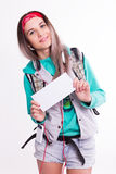 Young brunette female student standing and listening to music from your device. Beautiful young backpacker. Royalty Free Stock Photo