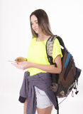 Young brunette female student standing and looking at her smartphone. Royalty Free Stock Images
