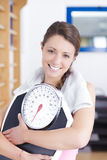 Young brunette fitness woman with scale Royalty Free Stock Photo
