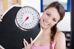 Young brunette fitness woman with scale. Portrait of young brunette fitness woman with scale Royalty Free Stock Image