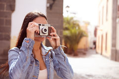 Young brunette focusing her old camera Stock Photos