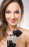 Young brunette getting makeup, with brushes. Stock Images