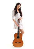 Young brunette girl with acoustic gui. Young beautiful brunette girl in white chemise with acoustic guitar, isolated on white stock photo