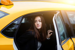 Young brunette girl in backseat of taxi with open door Royalty Free Stock Photo