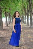 Young brunette girl in a beautiful blue dress. Royalty Free Stock Photos