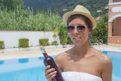 Young brunette girl in bikini holding bottle of wine Stock Photos