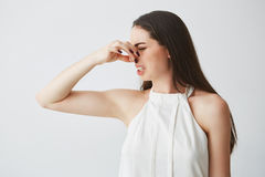 Young brunette girl closing covering nose over white background. Bad smell. Stock Image