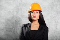 Young brunette girl in coat, helmet pose Royalty Free Stock Images