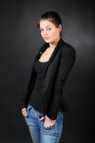 Young brunette girl in coat pose. Beautiful young brunette girl in coat pose, hold hands in pockets in photo studio, half body Royalty Free Stock Photo