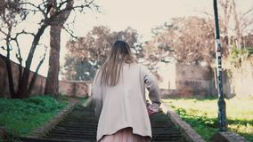 Young brunette girl coming up the stairs. Stylish woman walking in spring old town, bright sunlight in the morning. Young brunette girl coming up the old stock footage