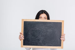 Young brunette girl covers her face with blank chalkboard Stock Photo