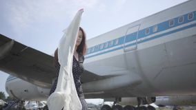 Young brunette girl in the dress with shawl in hands spinning around and running away in front of big plane. Joy of stock footage