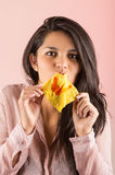 Young brunette girl eating chinese wonton cracker Royalty Free Stock Photography