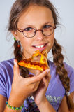 Young brunette girl eating a piece of pizza Stock Images