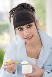 Young brunette girl eats a yogurt Royalty Free Stock Photos