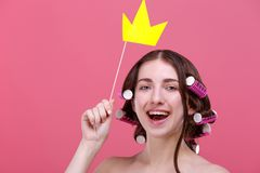 A girl holds a yellow paper crown over her head on a stick and smiles cute. On a pink background. royalty free stock images