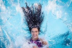 Young brunette girl falls backwards into a pool stock photography