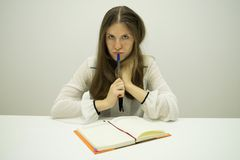 Young brunette girl with flowing hair sits at a table with a diary on the table royalty free stock image